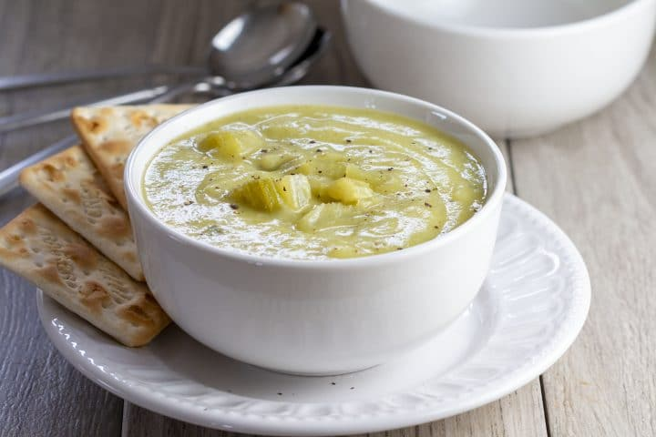 A bowl of Creamy Celery Soup with crackers on the side of the bowl