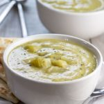 Two bowls of Creamy Celery Soup with crackers on the side of the bowl