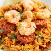 a plate of bright yellow saffron rice topped with chorizo and shrimp