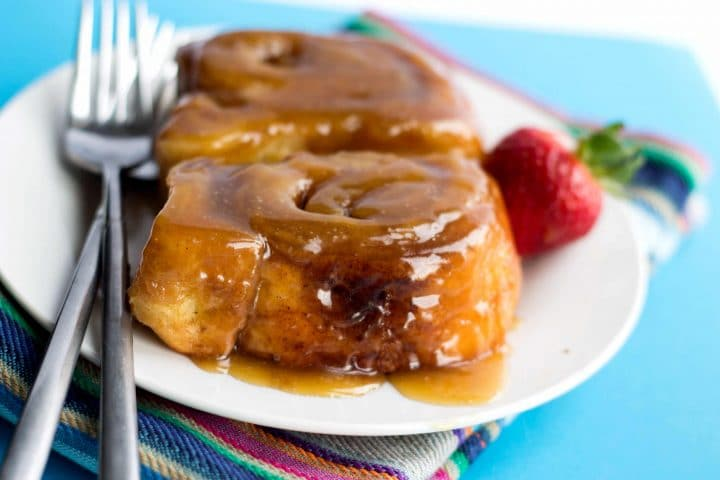 Two classic sticky buns on a white plate covered in sauce