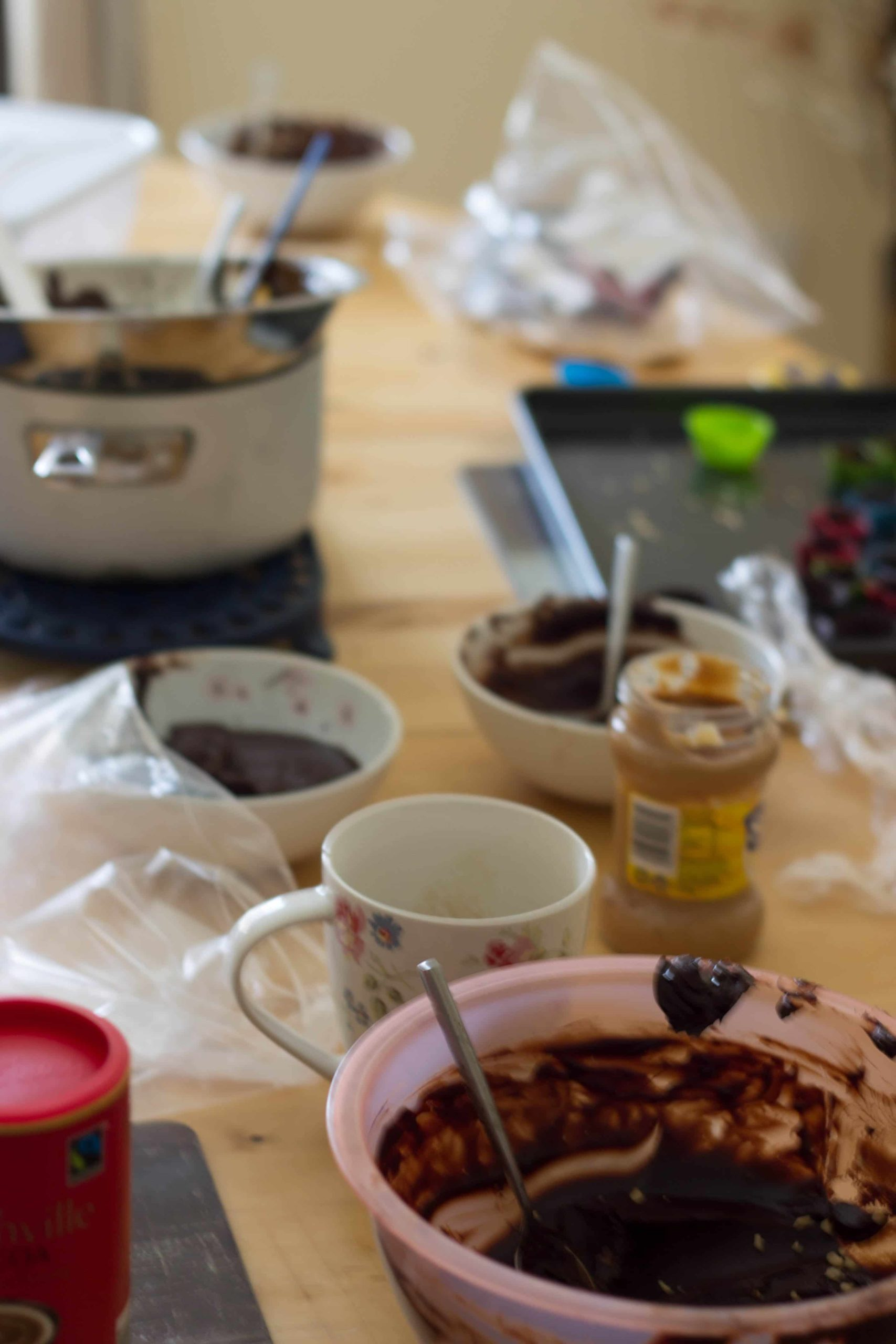 mess in the kitchen, bowls covered in chocolate, unopened jars and dirty pans.