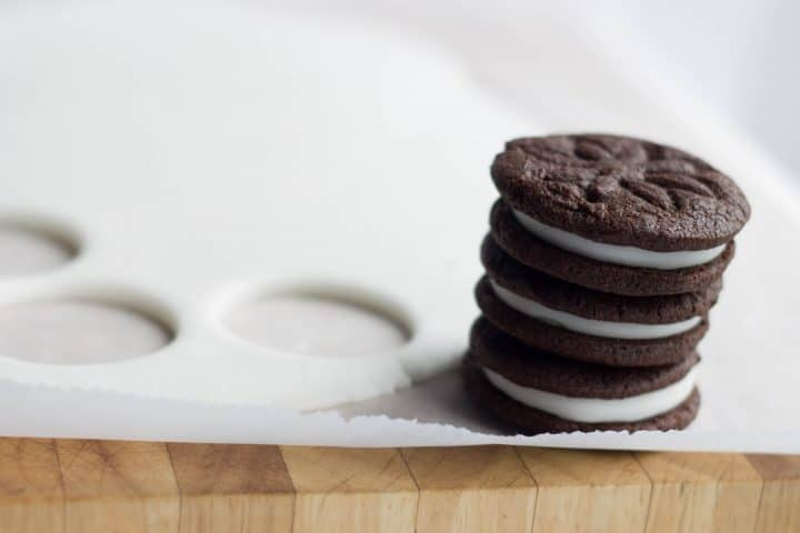 A stack of Homemade oreos next to the rolled out fondant with rounds removed