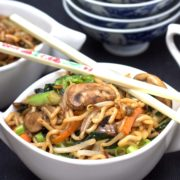 A bowl of food on a plate, with Noodles and chopsticks