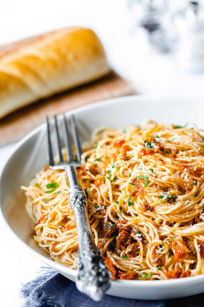 A plate of angel hair pasta with pesto sauce sprinkled with grated cheese and chopped parsley