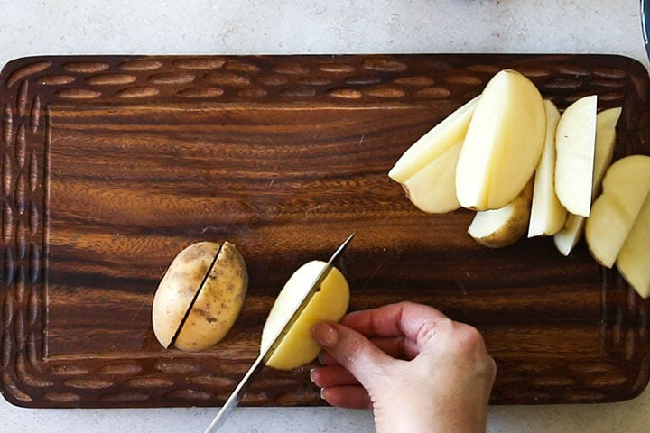 The raw potatoes on a cutting board being cut into wedges