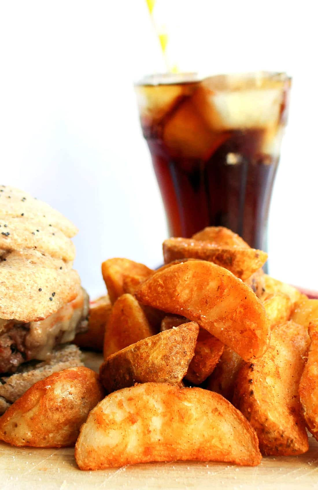 A plate of the Seasoned Baked Potato Wedges with a burger and a coke in the background.