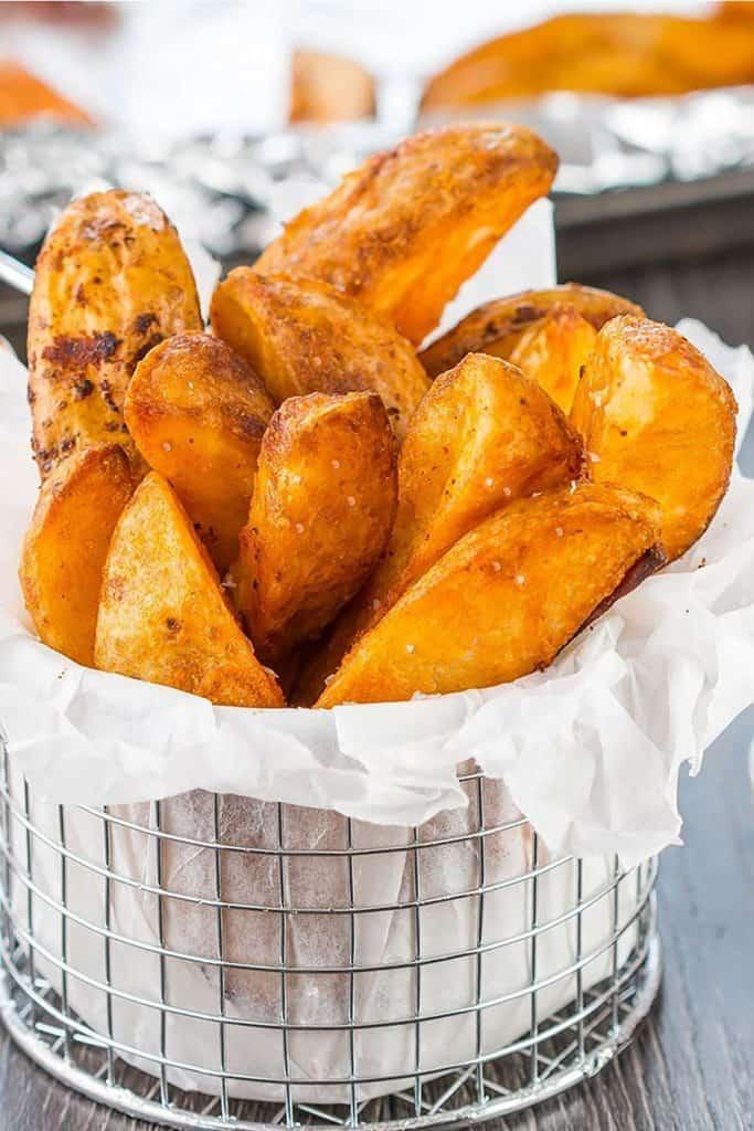 Seasoned Baked Potato Wedges in a metal serving basket sprinkled with salt