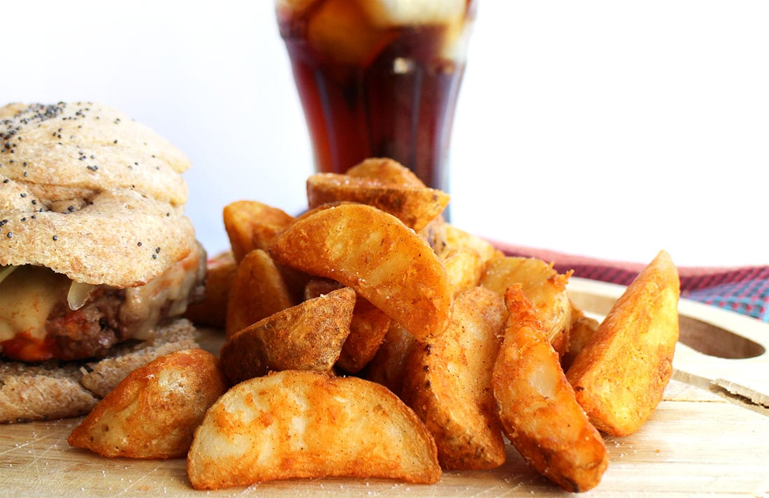 A pile of the crispy wedges on a cutting board next to a burger and a coke in the background.