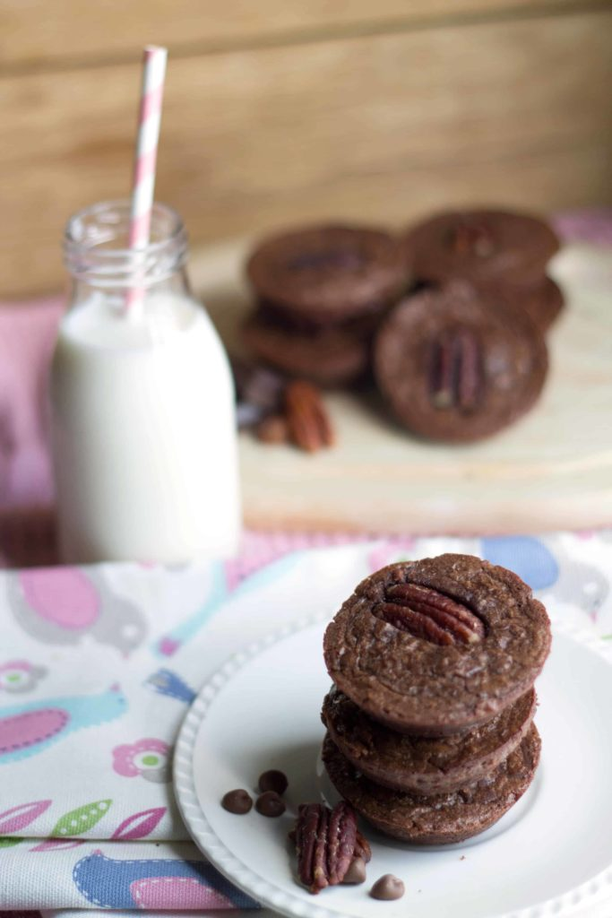 Triple Chocolate Brownie Bites on a plate with a bottle of milk and more brownies in the background.