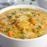 A bowl of soup, with Bacon and vegetables in it