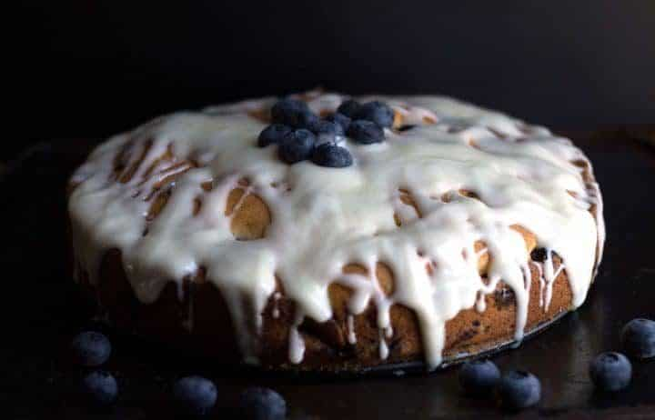 A blueberry cake with a cream cheese icing drizzled all over it topped with fresh blueberries.