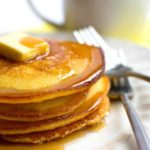 A Stack of bright yellow cornbread pancakes with a square of butter and syrup on top