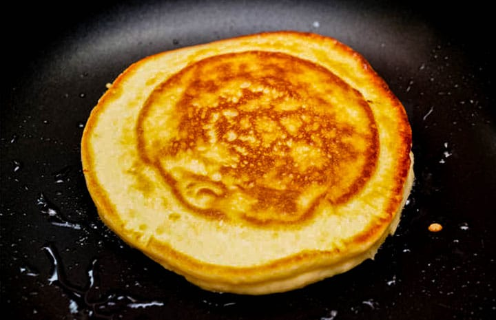 a cornbread pancakes cooking in a pan