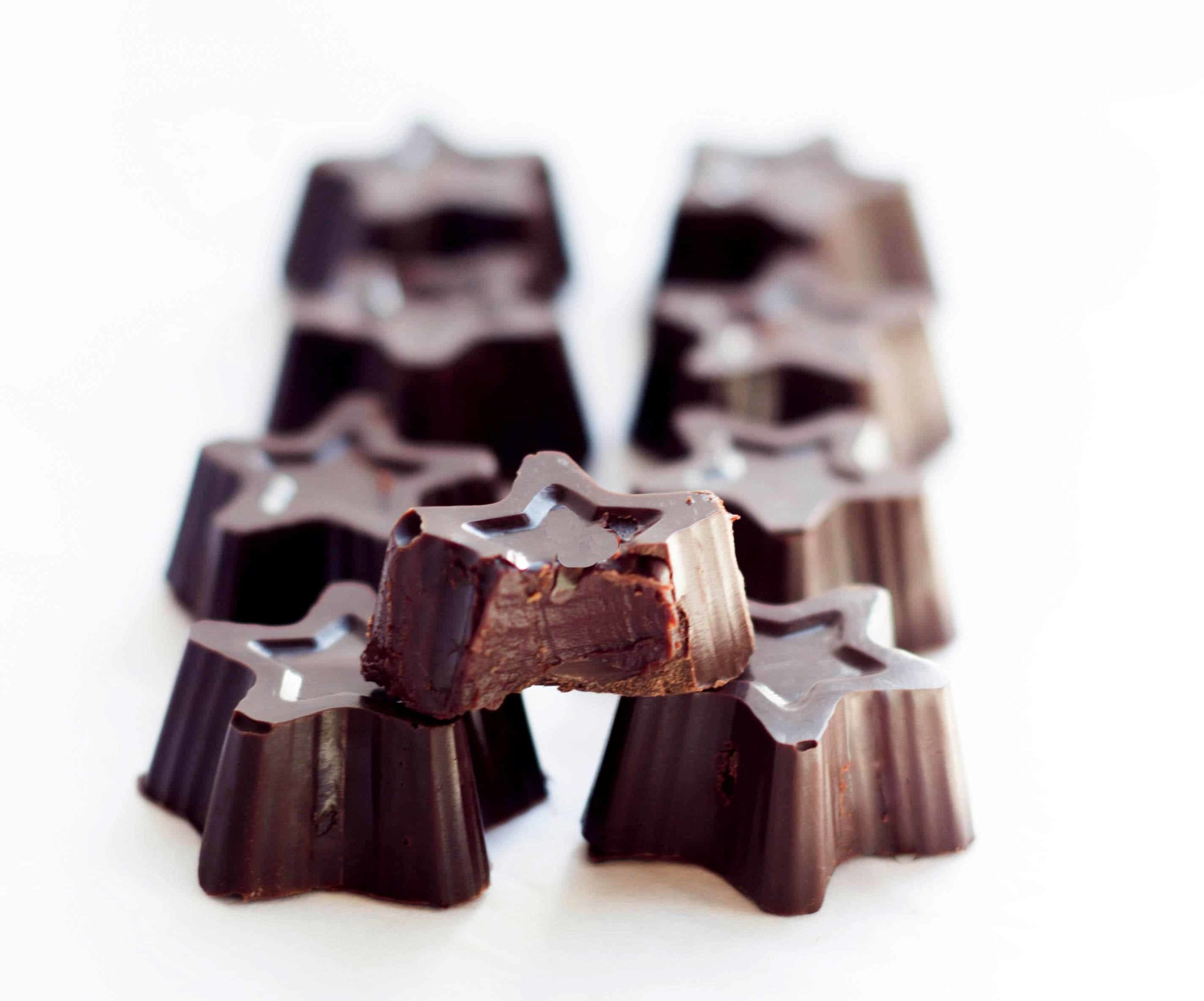 eight star shaped dark chocolate truffles with one in the front with a bite out of it.