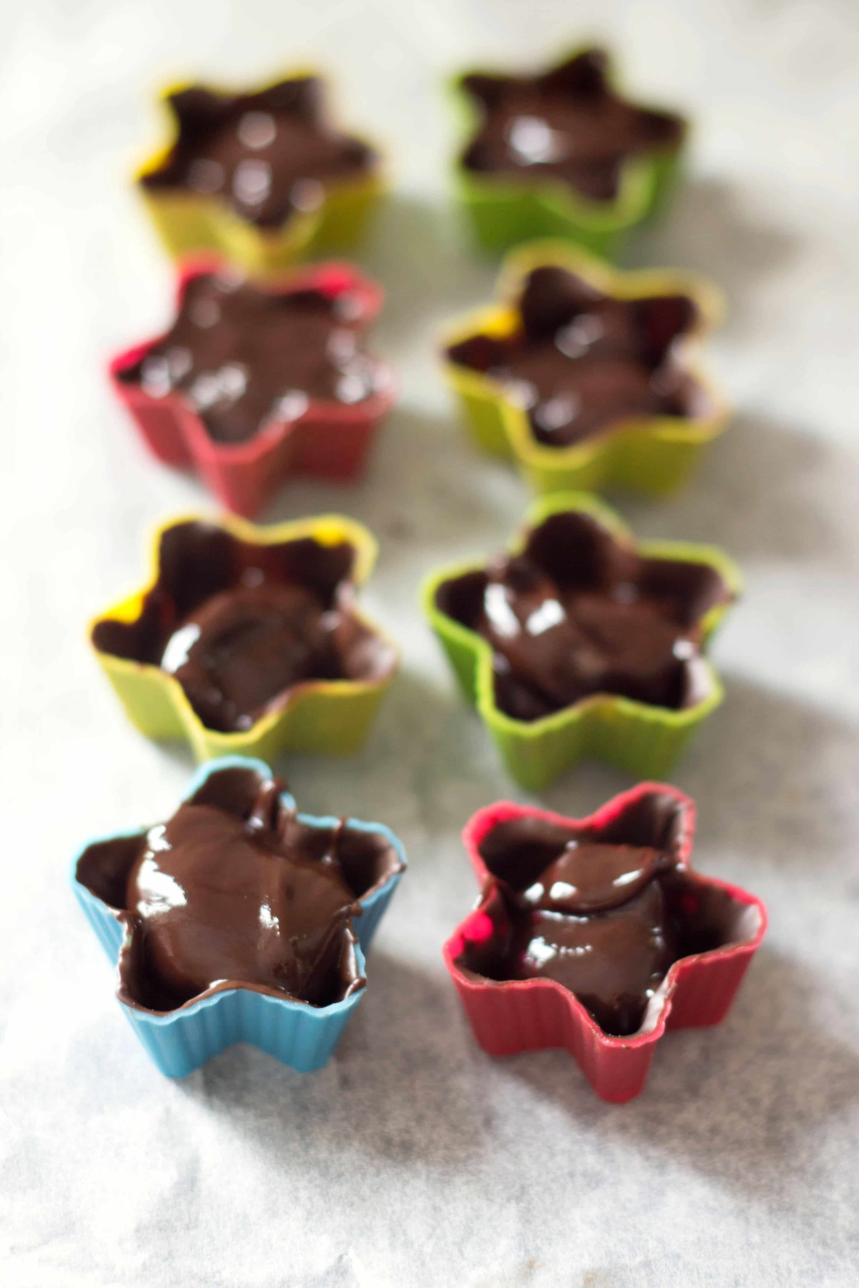 eight star shaped silicone moulds with dark chocolate truffles with melted chocolate in them.