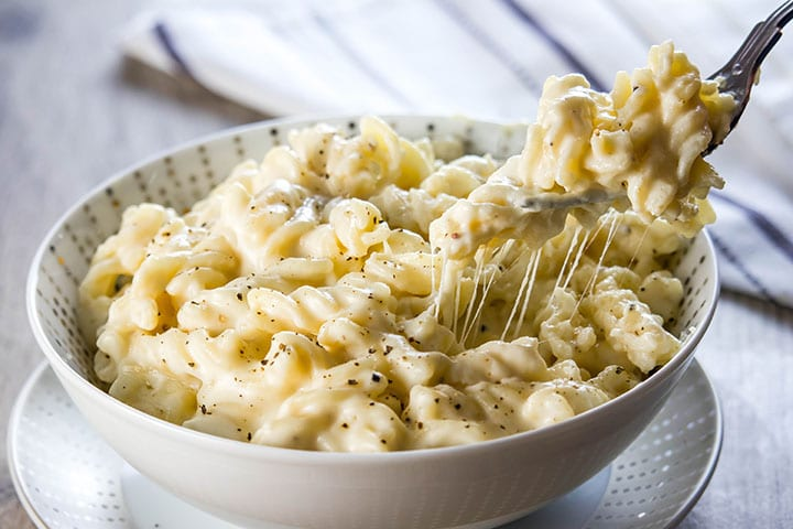 A fork digging into a big bowl of Homemade Creamy Mac and Cheese