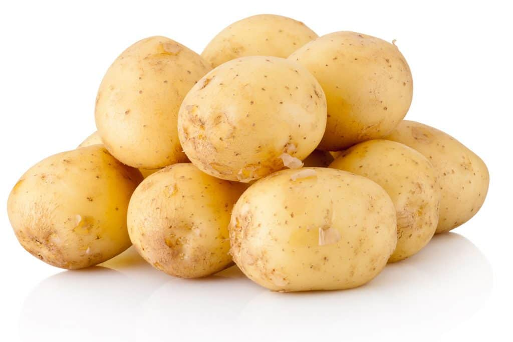 A pile of raw, unpeeled potatoes with a white background