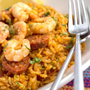 A close up of a white filled with yellow rice topped with shrimp and Chorizo