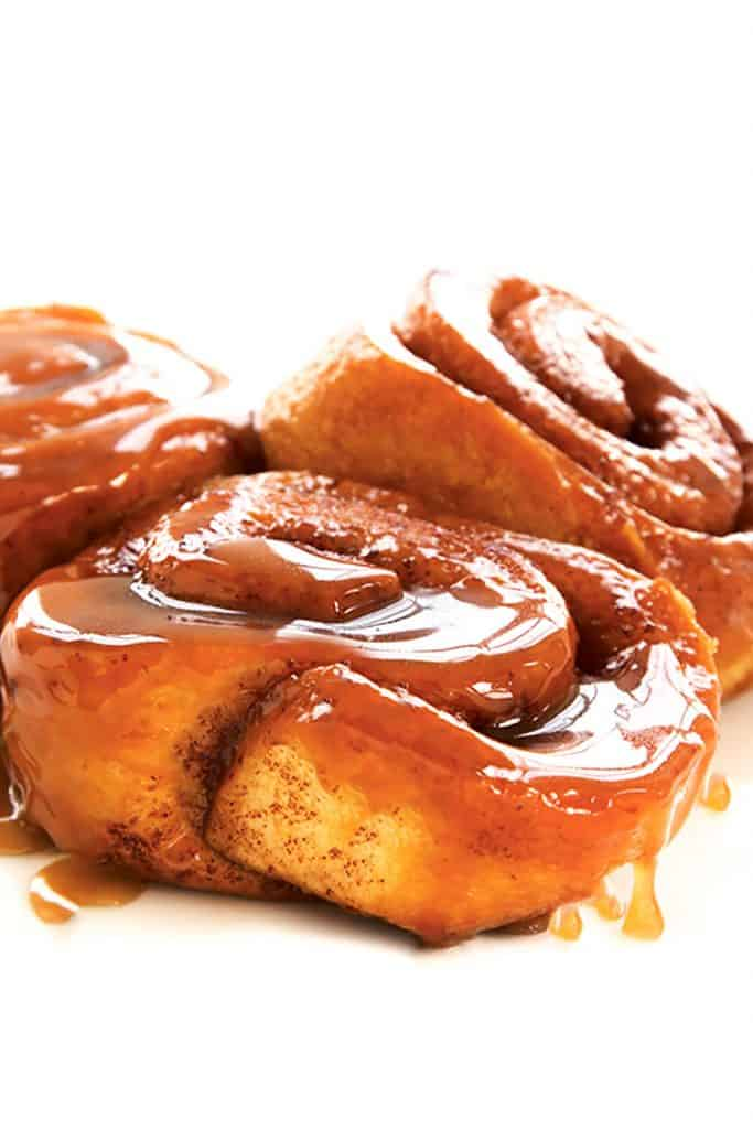 Three sticky buns covered in gooey sweet sauce