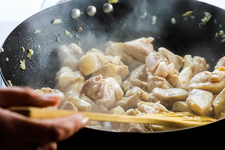 The chicken browning in the wok
