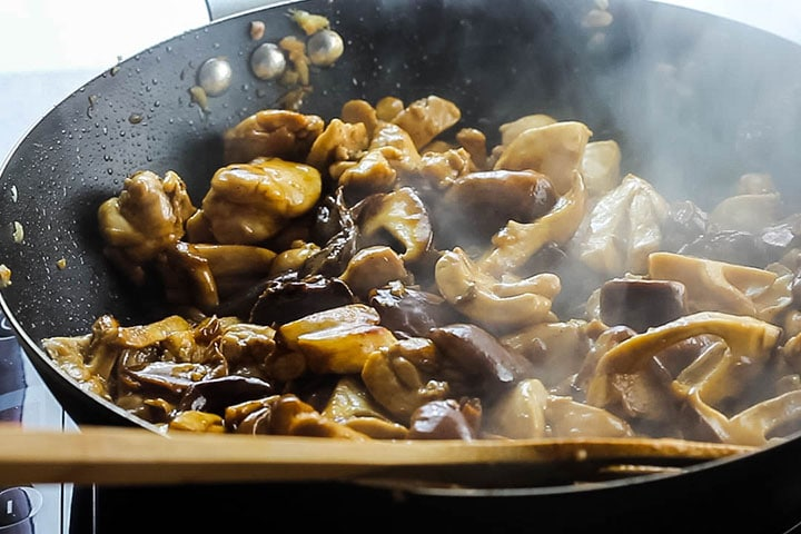 The soy sauce and oyster sauce added to the wok with the chicken and mushroom mixture