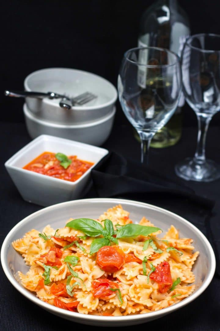 Easy Cherry Tomato Sauce on bow tie pasta in a plate topped with fresh basil leaves