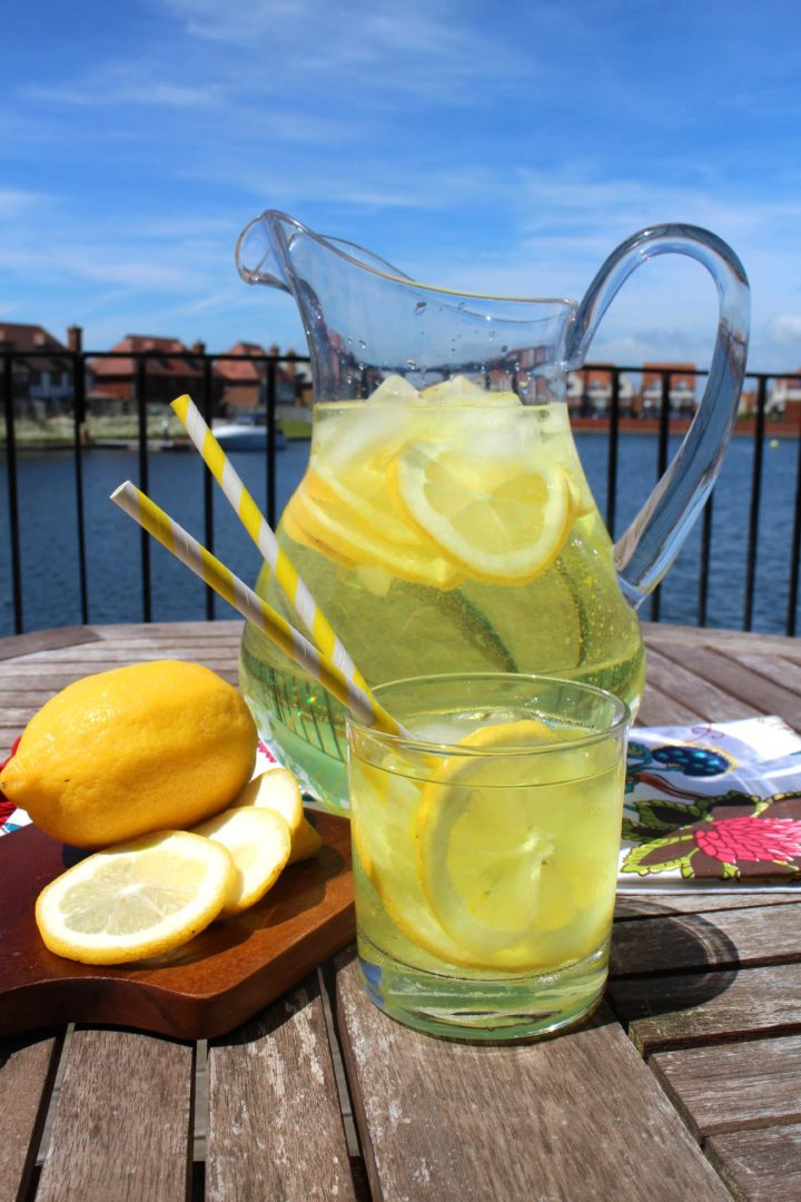 Erren's Hard Lemonade in a glass with a jug and lemons cut up on a chopping board, with a harbour view behind