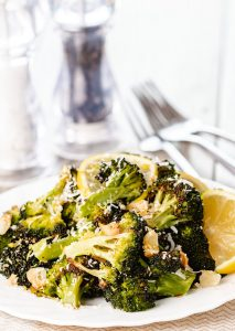 roasted broccoli piled high on a plate scattered with grated cheese and brown garlic