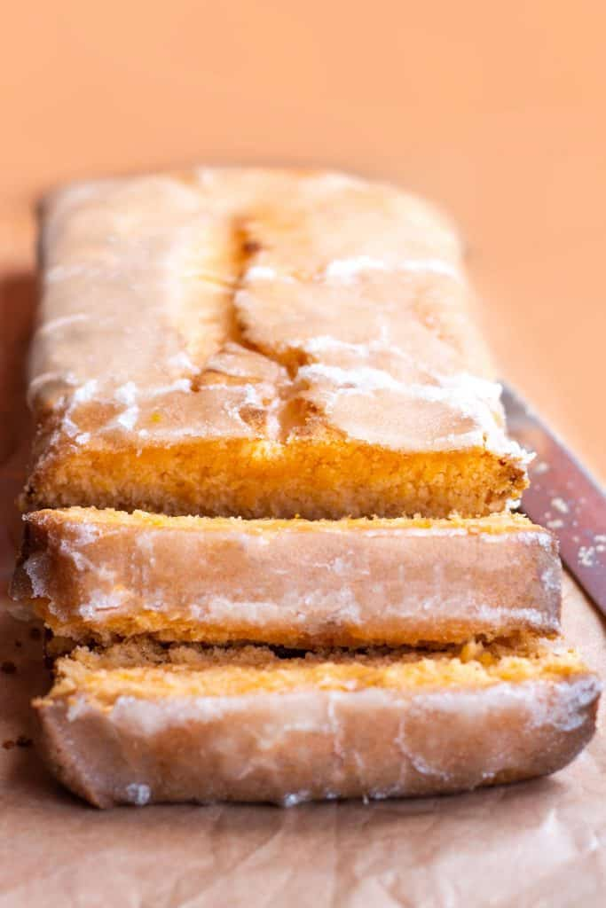 a tangerine loaf cake with drizzle icing sliced