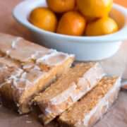 a tangerine drizzle cake sliced with a bowl of tangerines in the background