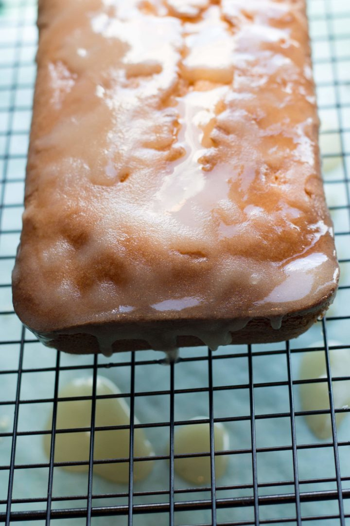 Tangerine Drizzle Cake on a cooling rack covered in sugar glaze