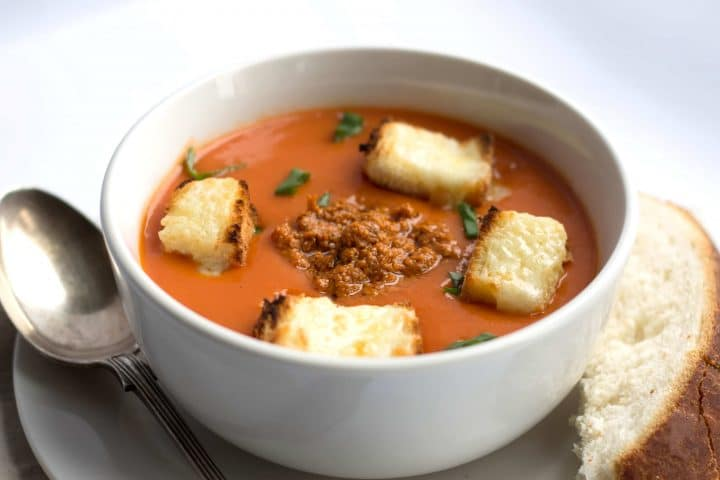 Tomato Soup with a spoonful of red pesto and with Cheesy Croutons in a bowl with a spoon and bread next to it