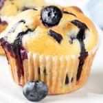 a blueberry muffin topped with a fresh blueberry with more muffins in the background