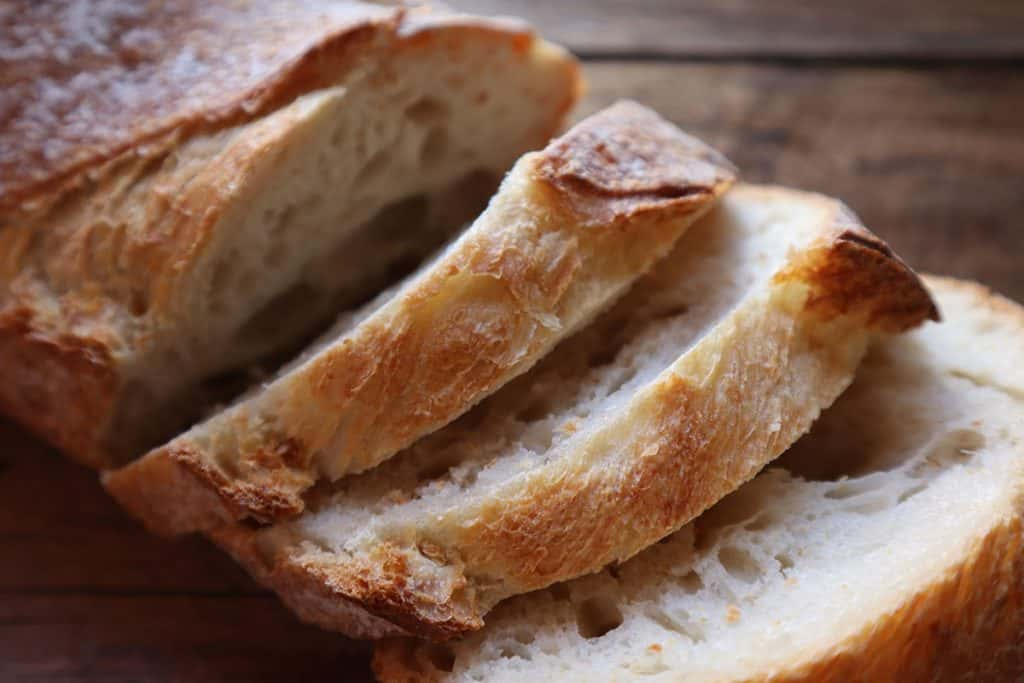 a loaf of crusty bread cut into thick slices
