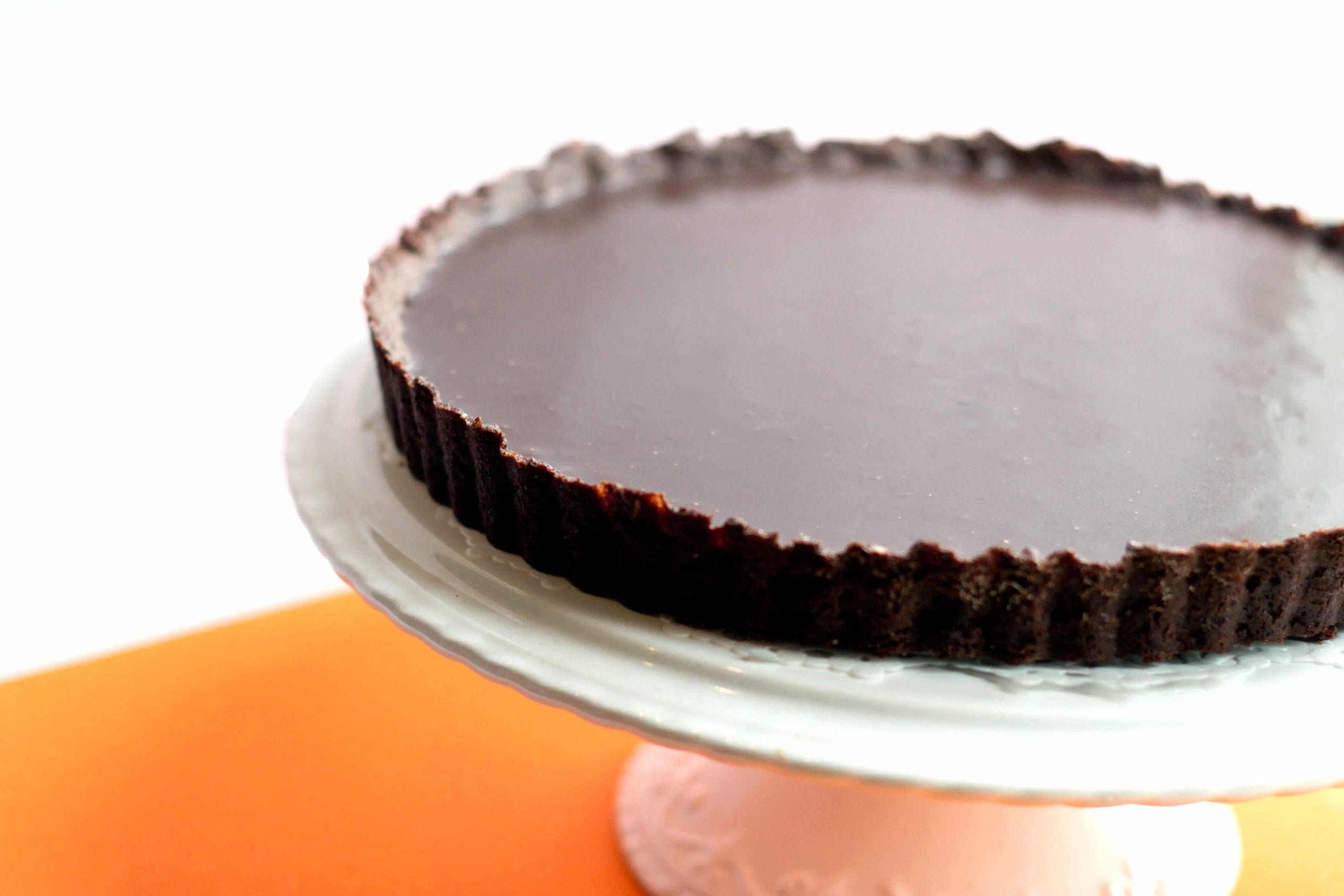 dark chocolate silk tart on a cake stand, undecorated