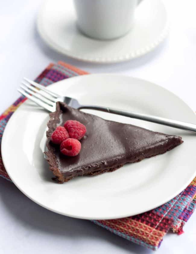 Dark Chocolate Silk Tart on a plate topped with fresh raspberries