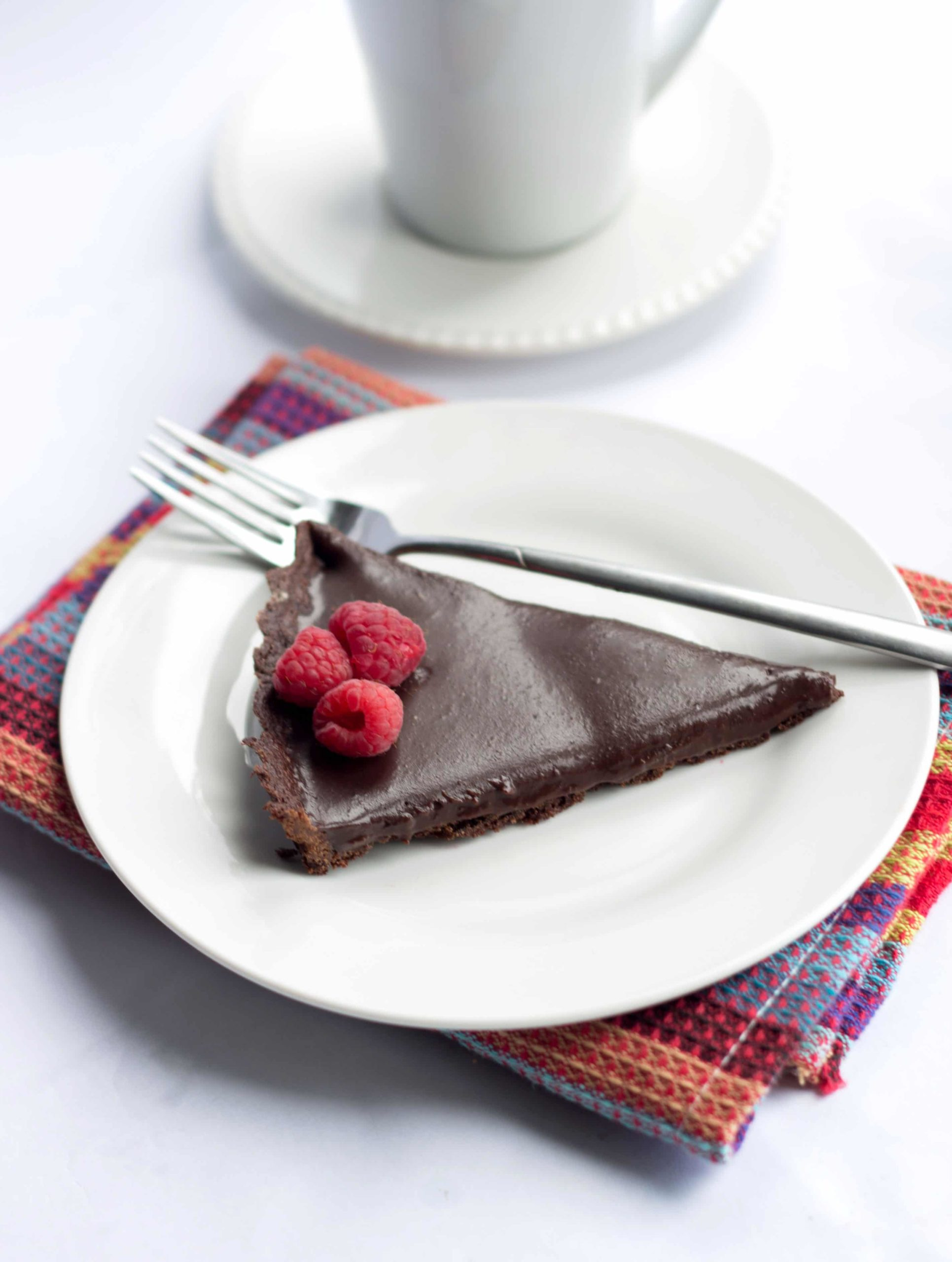 dark chocolate silk tart with three raspberries on a plate with a fork, cup and saucer in the background