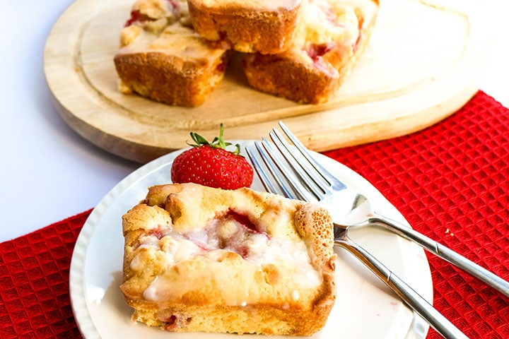 The Fresh Strawberry Cakes on a plate with two forks and more cakes in the background