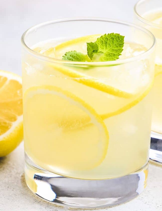a glass of Homemade Hard Lemonade garnished with lemon slices and a sprig of mint