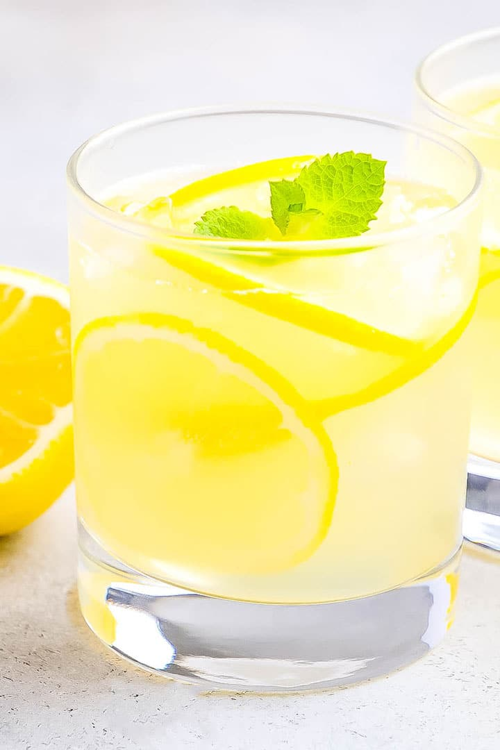 a glass of Hard Lemonade with lemons in the background and lemon slices and mint leaves in the glass