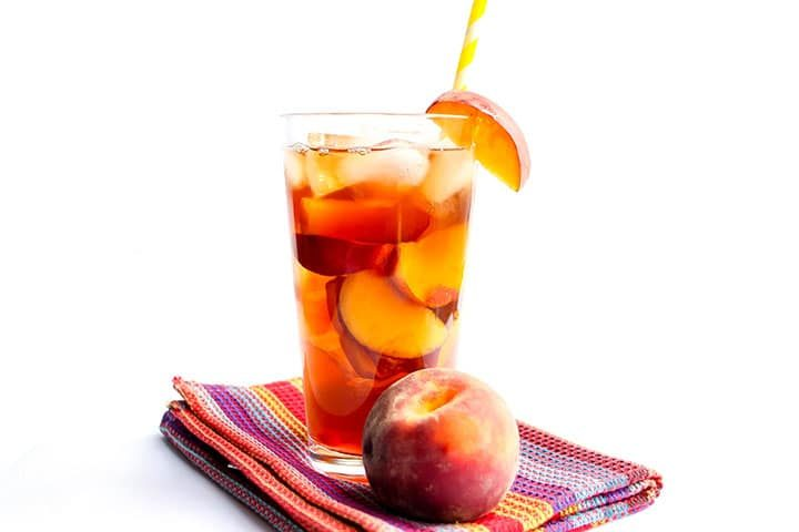 A glass of SweetPeach Iced Tea with ice and a straw and a fresh wedge of peach on the glass