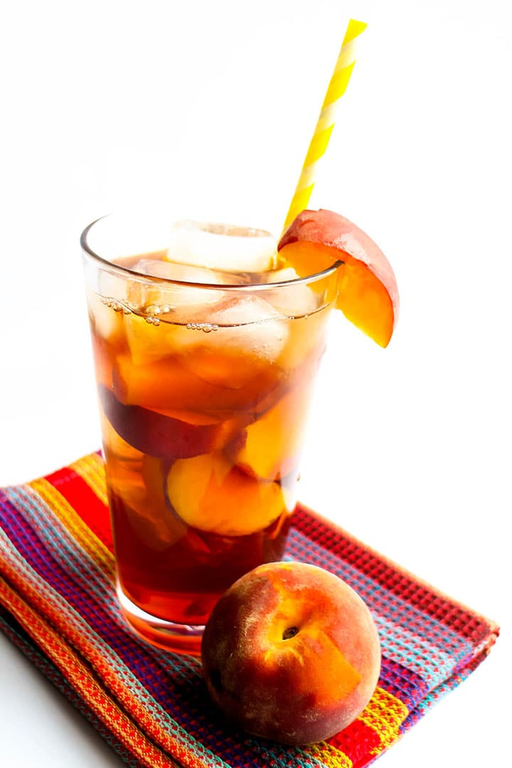 A glass of Sweet Peach Iced Tea with ice and a straw and a fresh wedge of peach on the glass