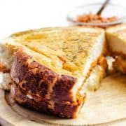 A golden grilled cheese sandwich on a cutting board with cheese oozing out of the middle