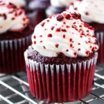 a Red Velvet Cupcakes with Cream Cheese Icing sprinkled with cake crumbs and more cupcake in the background