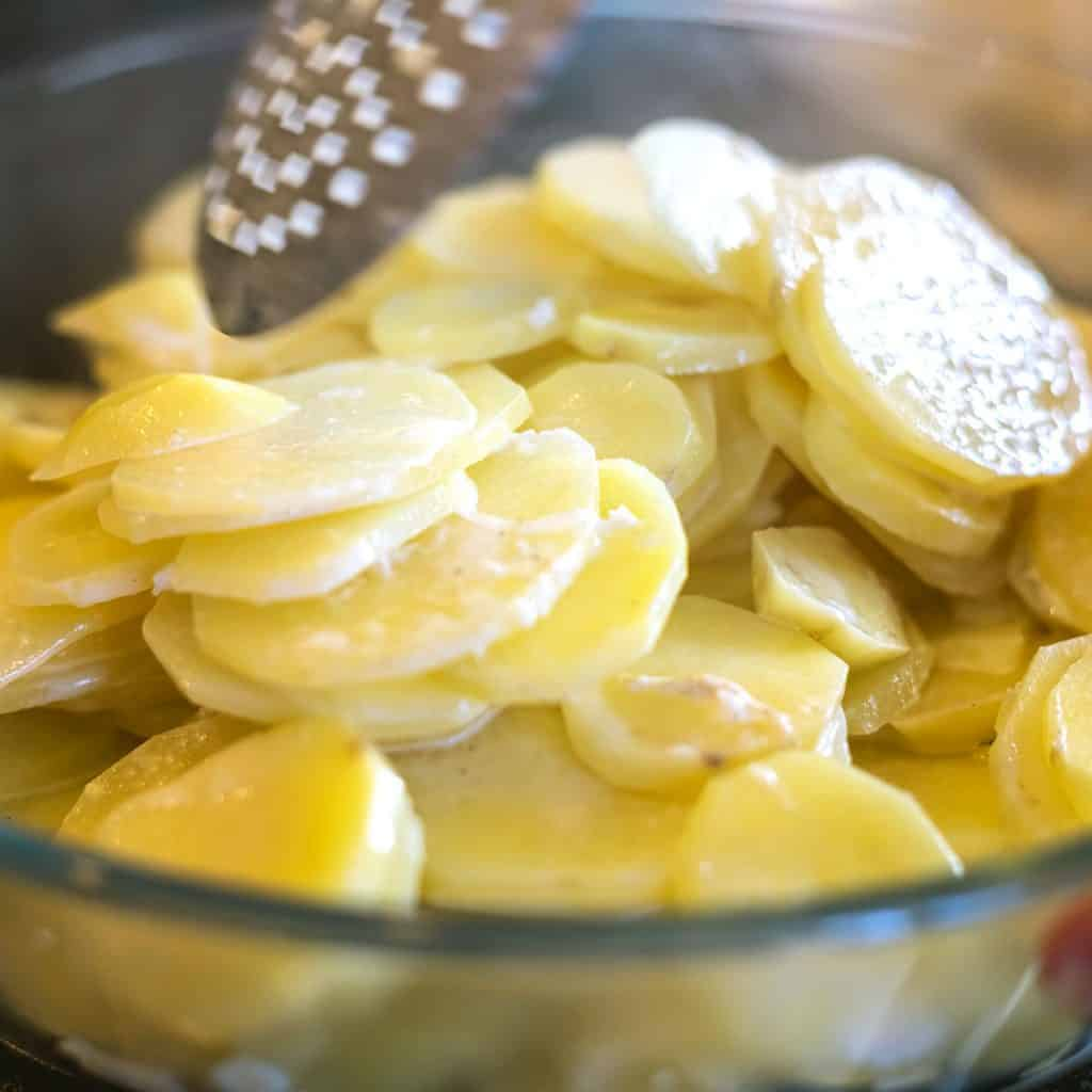 a bowl with cream and potato slices