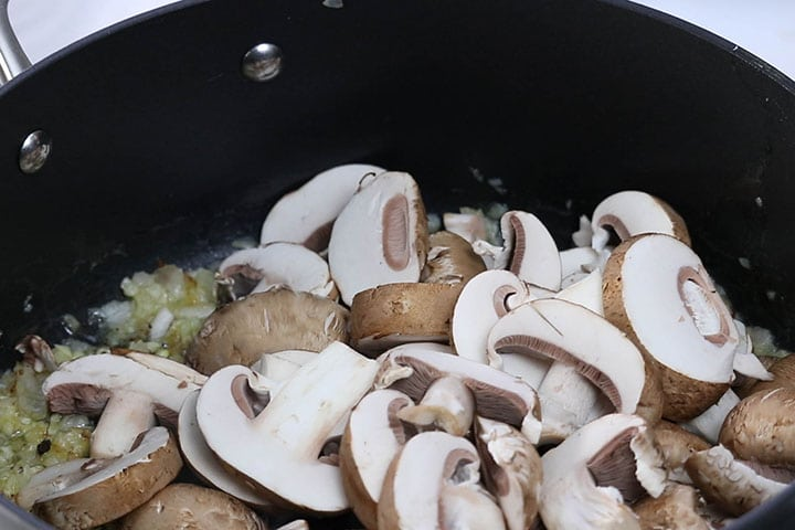 Mushrooms cooking in a pot with garlic and shallots