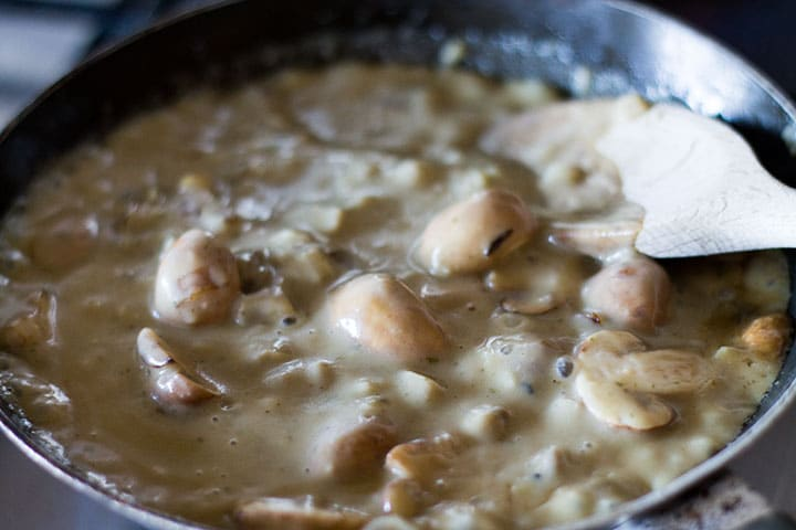 A pan with mushrooms in a bubbling cream sauce