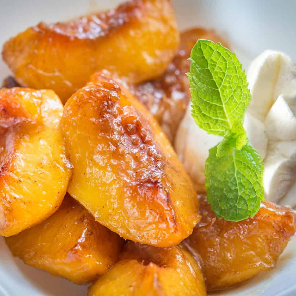 cooked peaches with cream served with a sprig of mint for decoration