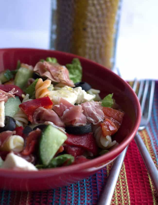 Antipasto Pasta Salad in a red bowl with dressing in the background