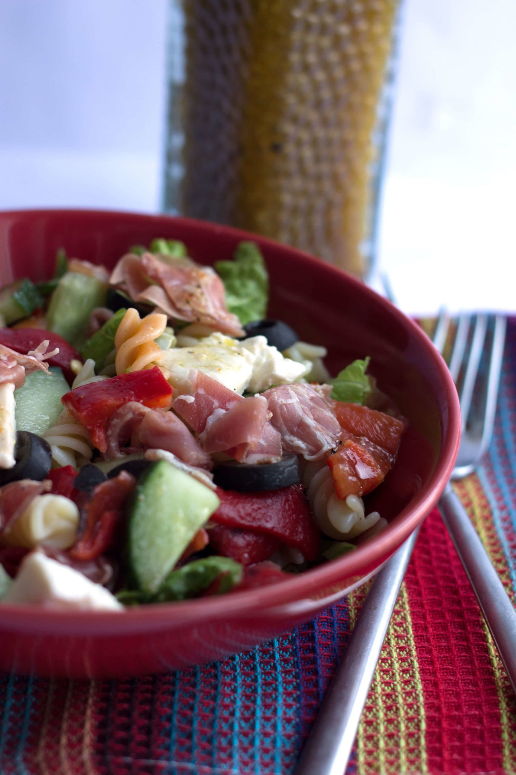Antipasto Pasta Salad in a dark red bowl with forks next to it